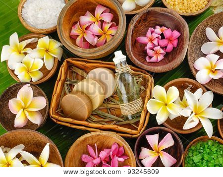 spa setting with oil, soap in basket ,colorful Frangipani in bowl, banana leaf
