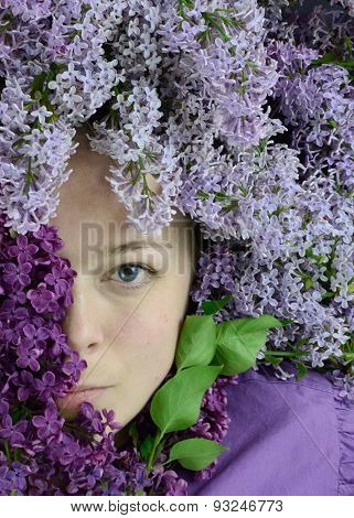 Close-up portrait of a woman covered in lilacs.