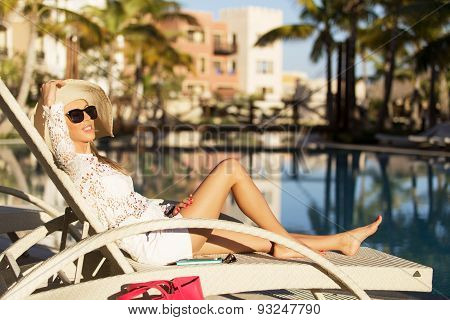 Lady relaxing in deck chair by the swimming pool