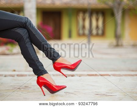 Woman in black leather pants and red high heel shoes sitting on bench