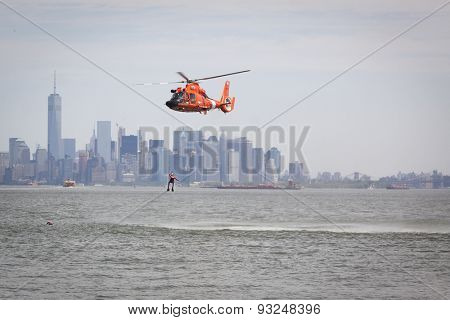 STATEN ISLAND, NY - MAY 24 2015: A Coast Guard rescue swimmer is hoisted by line from the water into a US Coast Guard MH-65 Dolphin helicopter for a Search and Rescue demonstration during Fleet Week.