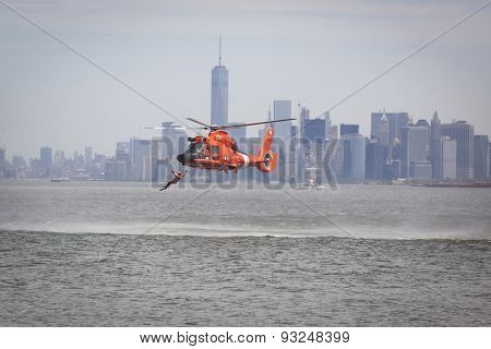 STATEN ISLAND, NY - MAY 24 2015: A Coast Guard rescue swimmer leaps from a USCG MH-65 Dolphin helicopter into the water during a Search and Rescue demonstration at Sullivans Pier for Fleet Week 2015.