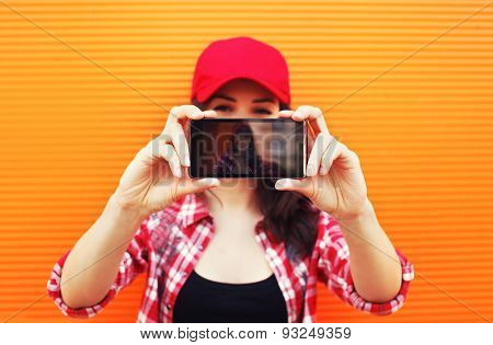 Technology And People Concept - Pretty Girl Makes Self-portrait On The Smartphone Outdoors Against C