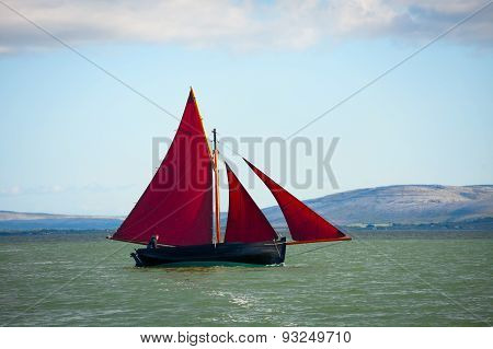Traditional wooden boa Galway Hooker with red sail compete in regatta. Ireland.