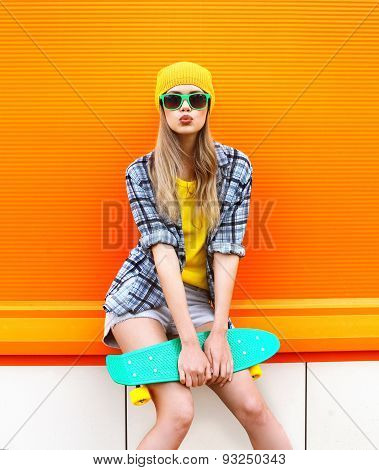 Fashion Hipster Cool Girl In Sunglasses And Colorful Clothes With Skateboard Having Fun Against The