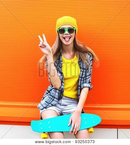 Fashion Portrait Of Hipster Cool Girl In Sunglasses And Colorful Clothes With Skateboard Having Fun
