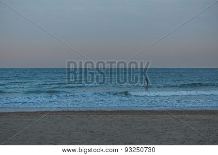 Golden Sunset Light Of A Surfer On A Surf Board At The Beach With Sand And No Clouds In The Sky In E
