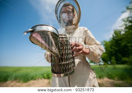 beekeeper with smoke tool