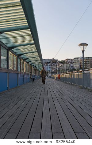 A Guy In His Army Suit Walking Away From The Camera, Walking At The Pier At Sunset Hour On A Summer