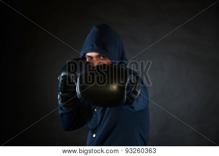 Hooded Man In A Fighting Stance With Black Boxer Gloves.