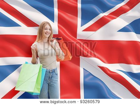 A Happy Young Woman With The Colourful Shopping Bags From The Fancy Shops. Great Britain Flag Backgr