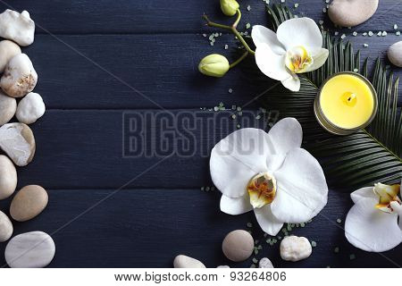 Still life with beautiful blooming orchid flower, candles and pebbles, on wooden background