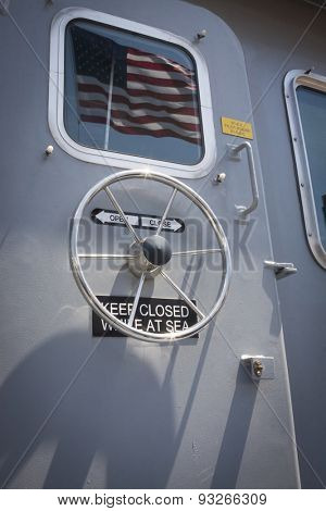 NEW YORK - MAY 22 2015: The American Flag reflected on a door window of a US Naval Academy Yard Patrol Craft used for at-sea training and research, moored at Pier 86 during Fleet Week NY 2015.