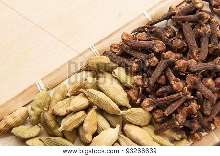 Oriental spice: cardamom seeds and cloves on wooden spoon