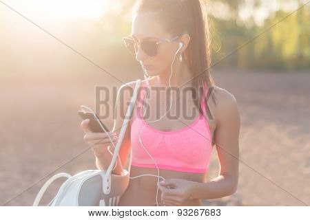 Athlete woman listening music looking at smartphone after workout in nature outdoors portrait summer