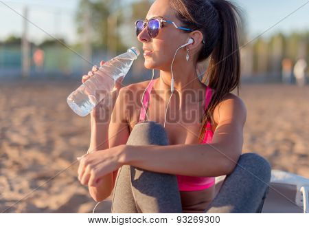Beautiful fitness athlete woman drinking water after work out exercising on summer in beach outdoor