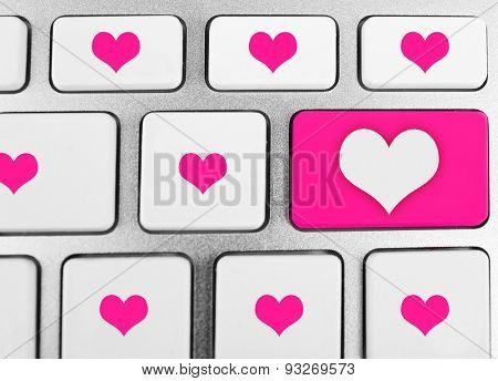 Close up of laptop keyboard with hearts icons
