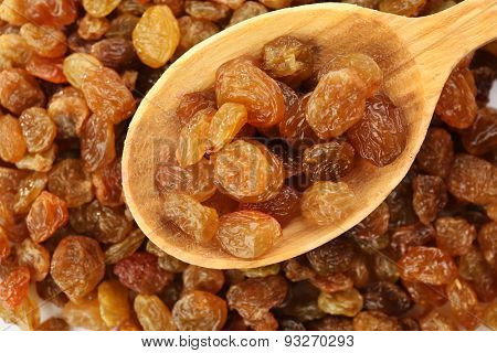 Raisins in wooden spoon on raisins background
