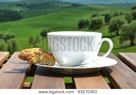 Coffee cup and cantuccini on the wooden table against olive grove. Tuscany, Italy