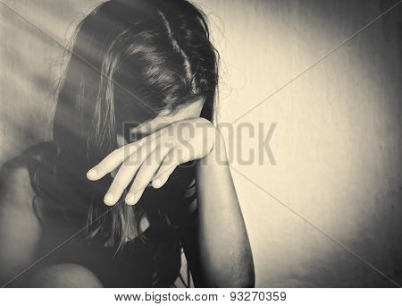Monochrome portrait of a sad and lonely girl crying with a hand covering her face (with space for text)