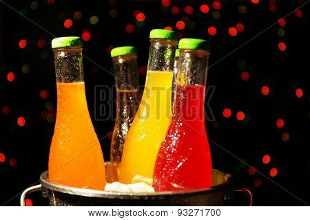 Alcoholic cocktails in metal bucket with ice cubes on dark bright background