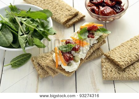 Crispbread with cream cheese, sun-dried tomatoes, herbs