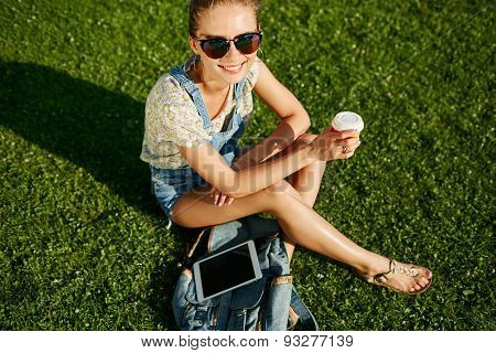 Close Up Portrait Of Young Blonde Girl With Coffee And Tablet Outdoor Sitting On Grass And Smiling.