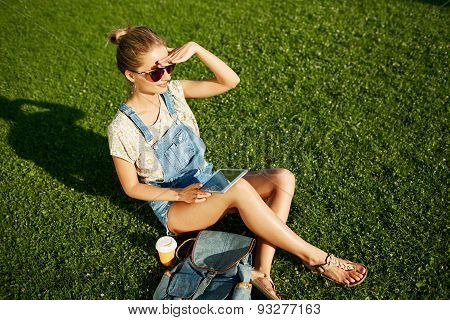 Young Happy Blond Girl Looking Into The Distance With Coffee And Pc Tablet Outdoor Sitting On Grass