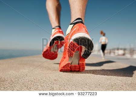 Close Up Runner Feet. Man Runner Legs And Shoes In Action On Road Outdoors At Road Near Sea. Male At