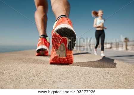 Runner Feet Running On Road Closeup On Shoe. Sportsman Fitness Sunrise Jog Workout Welness Concept.