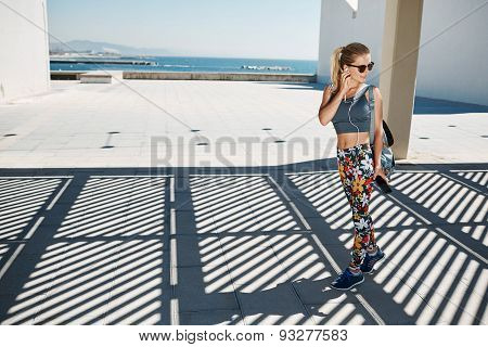 Young Fitness Blonde Woman In Sportswear Listening Music With Headphones After Training Outdoors At