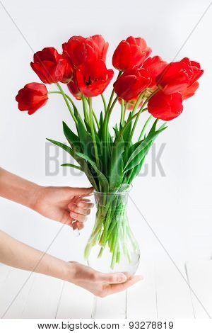 Tender Hands Hold Tulips Bouquet In Vase On Wood Table