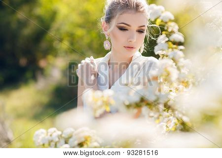 Beautiful happy woman in a flowery spring garden.