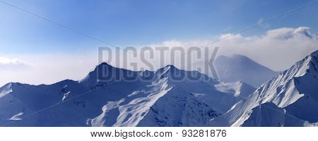 Panorama Of Snowy Mountains In Early Morning Fog