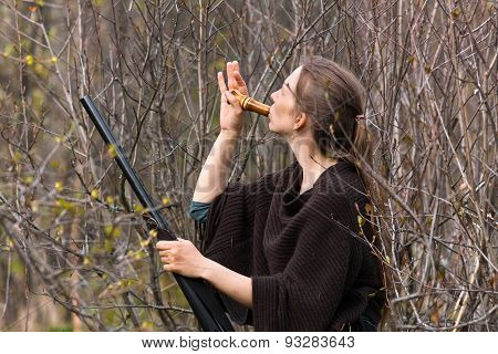 Woman Hunter In Shrubs With A Wooden Duck Call