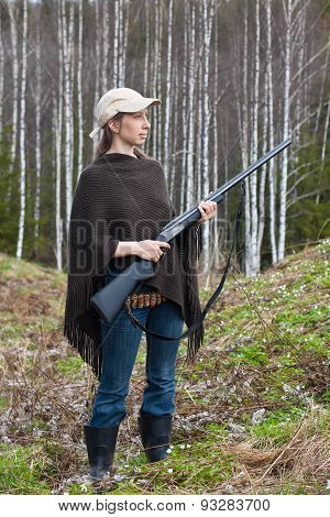Female Hunter With Gun In The Forest