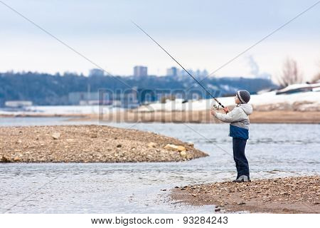Boy Fishing On Spinning On The River