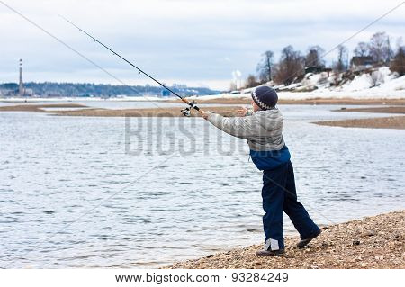 Boy Fishing On Spinning On The Riverbank