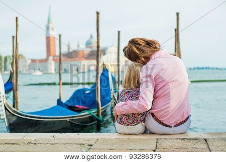 Mother And Daughter Sitting Together Cuddling At Water's Edge