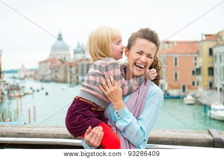 Laughing Mother Holding Daughter Who Is Whispering In Her Ear