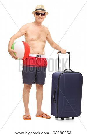 Full length portrait of a senior in swim shorts holding a beach ball and a bag isolated on white background