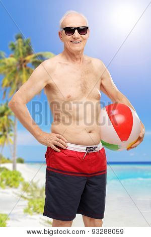 Vertical shot of a senior in swim shorts holding a beach ball at a beach and looking at the camera