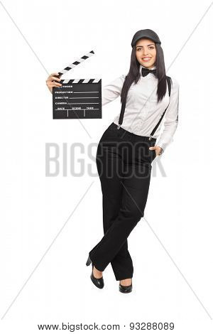 Full length portrait of a female movie director in an artistic outfit and holding a clapperboard isolated on white background