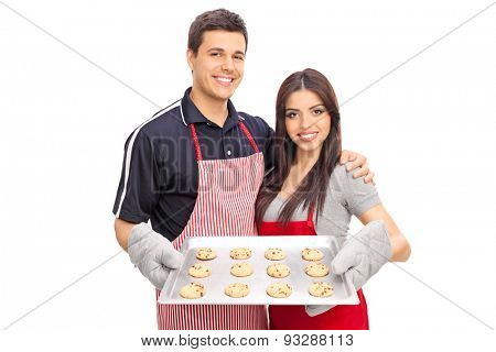Young couple with aprons holding a baking pan full of chocolate chip cookies isolated on white background