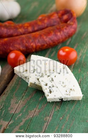 Three Slices Of Danish Blue Cheese In Front Of Spicy Sausages