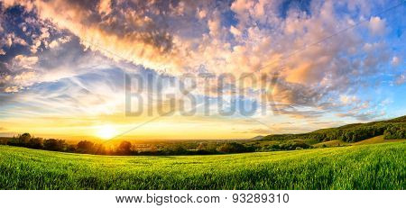 Panorama Of A Colourful Sunset On A Green Meadow