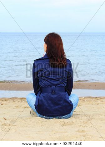 Woman Sitting On The Beach And Looks At Sea