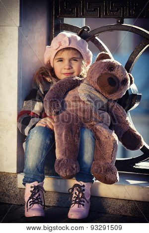 Little Girl In A Pink Beret Sits At A Fencing Of The Bridge And Holds A Toy Bear In Hand. Art Proces