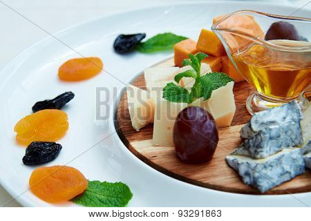Cheese and fruits on the wooden plate