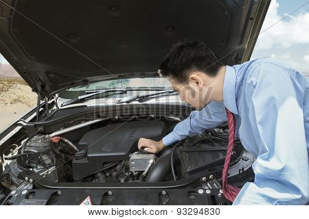 Man Checking The Broken Car Machine